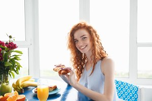 Happy young redhead lady sitting at the table eating croissant