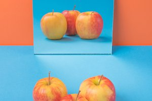 Apple on blue table isolated over orange background