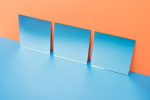 Mirrors on blue table isolated over orange background