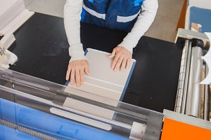 The operator of printing production pulls a printed sheet of paper