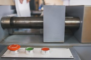 Red button on control panel of folding machine - printing polygraph industry, close up
