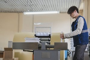 Worker and printing machine, polygraph industry - close up