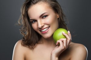 Beautiful smiling brunette girl holding a green apple