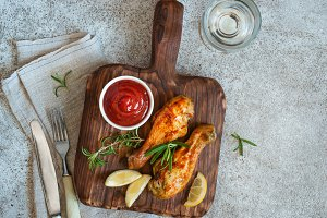 Grilled spicy chicken drumstick is served on a wooden board. Top