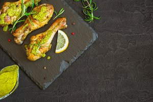 Roasted chicken drumstick In green sauce with lemon on a black b