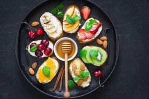 Assorted summer sweet snacks. Bruschetta or sandwiches with frui