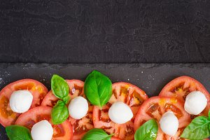 Fresh italian caprese salad  on dark plate. Top view with copy s