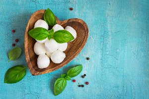 Mozzarella cheese and basil In a wooden bowl on a turquoise tabl