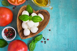 Mozzarella cheese, tomatoes and basil on a turquoise table.  Top