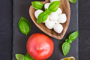 Mozzarella cheese, tomatoes and basil on a black stone table. Co