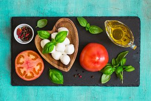 Mozzarella cheese, tomatoes and basil on a turquoise table. Conc