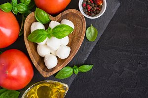 Mozzarella cheese, tomatoes and basil on a black stone table. To