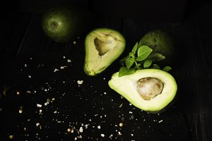 Avocado and spices on black wooden table with fruits, selective focus, concept