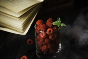 glass with ripe raspberries and mint on the background of books , selective focus, concept