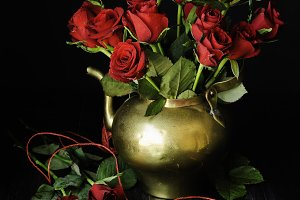 Bouquet of red roses in a copper jar with scissors selective focus, concept