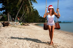 girl in a christmas hat on a swing on the beach