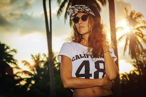 Young woman in baseball cap on sunset background