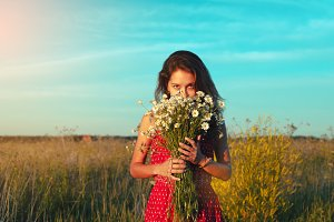 Cute girl with a bouquet of daisies in field