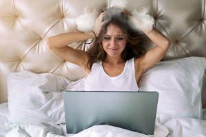 Young woman with laptop's holding her steamed head