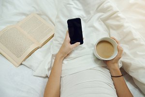 Female hands with a cup of coffee, phone and old book