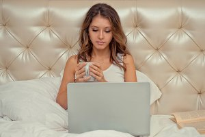 Womanwith laptop in a bed