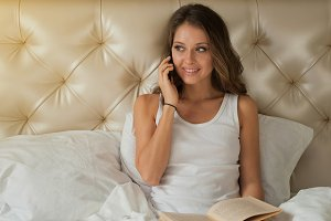 Happy beautiful woman with phone in the bed