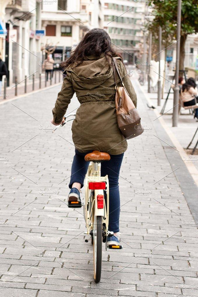 Woman cycling down the street.jpg - Transportation