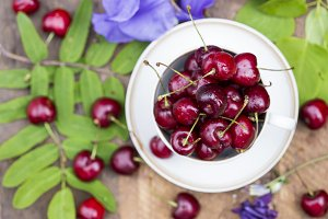 Cherries in the cup on wooden table