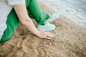 woman in green pants on beach