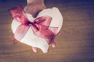 Hand holding a white fabric heart