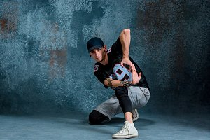 Young man break dancing on wall background.