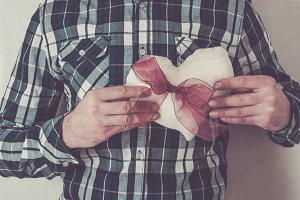 Man in plaid shirt holding a heart