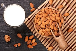Almond milk in a glass and almonds in wooden bowl on black stone background. Top view