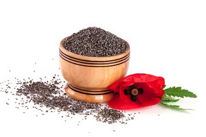Poppy seeds in a wooden bowl with a flower