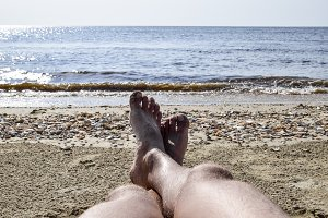 The legs of a man on a beach background. A man lies on an amatrace on the beach and is resting. Legs in the frame.
