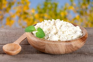 Cottage cheese in a wooden bowl on board with blurred garden background