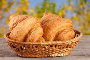 two croissant in a wicker basket on a wooden board with a blurry garden background