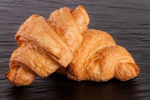 two croissant on black stone background closeup