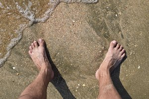 Legs men on the sea sand near sea wave
