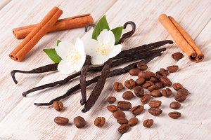Vanilla sticks and coffee beans with cinnamon on a white wooden background