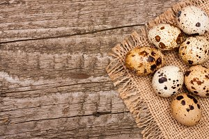 Several quail eggs on burlap on old wooden background with copy space for your text. Top view