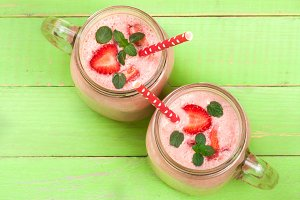 Glass of strawberry yogurt or smoothie with mint leaves on green wooden background. Top view