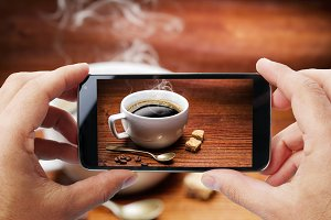 photo of cup of coffee by smartphone