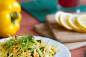 Fresh summer salad with cabbage, carrots and greens
