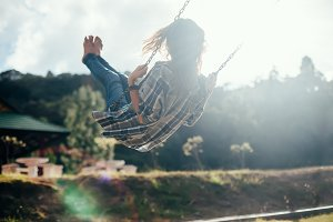 barefoot girl on swing in sun light