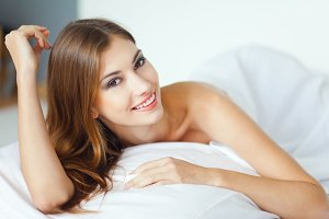 happy smiling young woman on bed