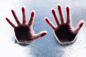 hands behind wet glass