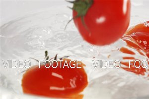 Few Red tomatoes, fruits plunging in water with splash