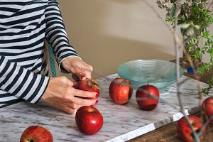 woman cutting red apple.