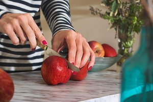Woman cutting apples on the table
